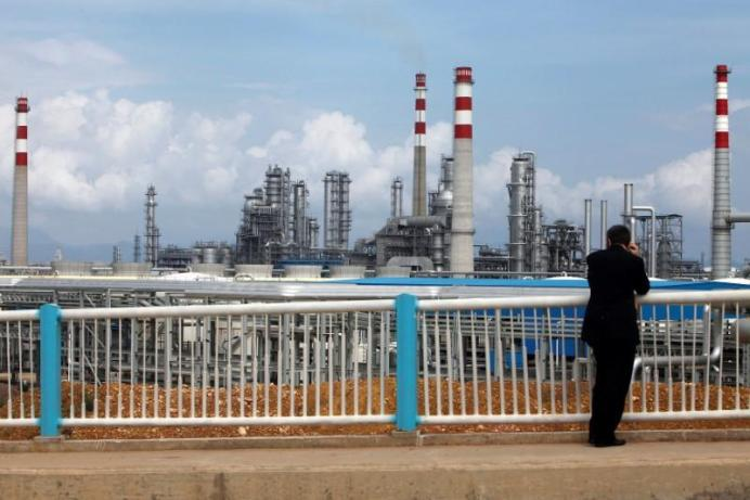 FILE PHOTO: A visitor looks at China National Offshore Oil Corporation's (CNOOC) oil refinery in Huizhou, China's southern Guangdong province. REUTERS/Tyrone Siu