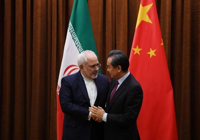 Iranian Foreign Minister Mohammad Javad Zarif (L) is greeted by Chinese Foreign Minister Wang Yi. REUTERS