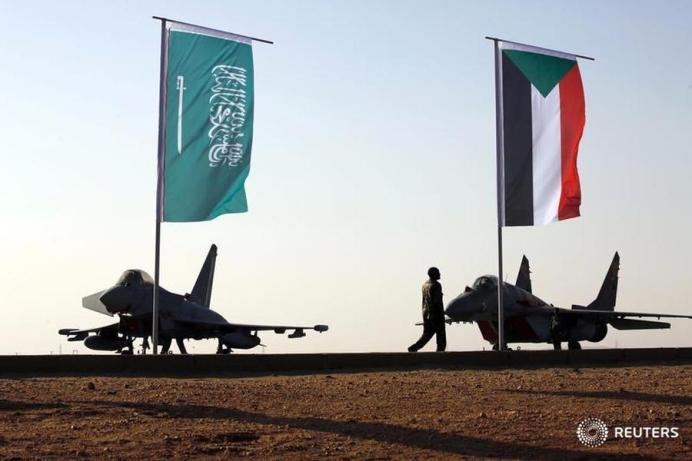 FILE PHOTO: Military personnel walk past the flags of Saudi Arabia and Sudan as Sudan's President Omar Ahmed al-Bashir attends the final training exercise between the Saudi Air Force and Sudanese Air Forces at Merowe Airport in Merowe, Northern State, Sudan April 9, 2017. REUTERS