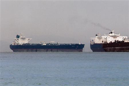 "Vessels sail past Malta-flagged Iranian crude oil supertanker ""Delvar"" anchoring off Singapore"