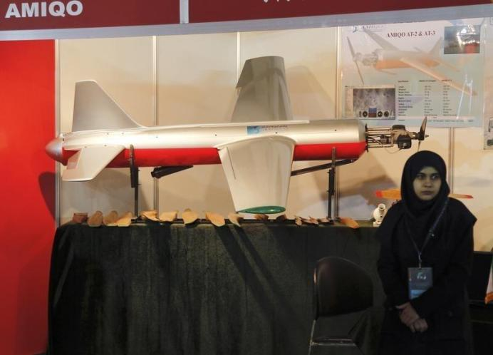 FILE PHOTO: An Iranian exhibitor stands beside an unmanned drone aircraft during Iran's Hi-Tech Expo opening at the Fairgrounds, near Damascus. REUTERS./
