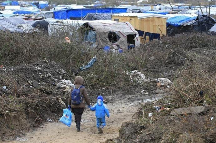 """A migrant and her child walk in the southern part of a camp for migrants called the """"jungle"""", in Calais, northern France, February 25, 2016. REUTERS/Pascal Rossignol"""