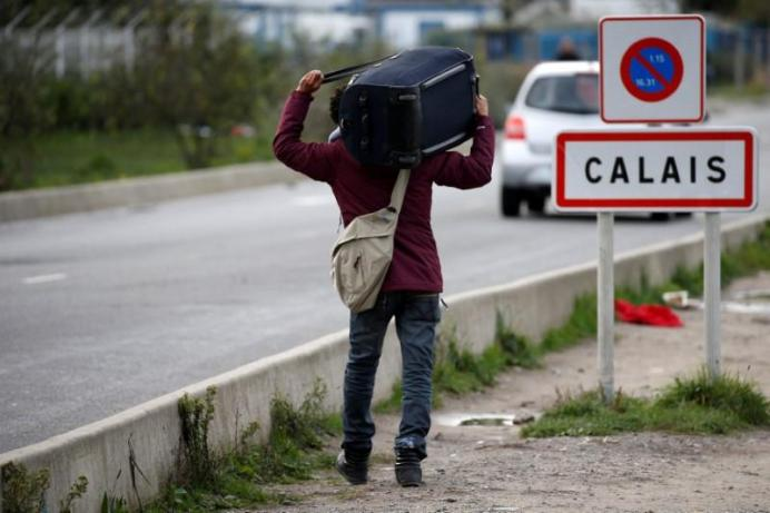 A migrant carries his belongings as they depart the Calais camp called the 'Jungle', France, October 22, 2016. REUTERS/Pascal Rossignol