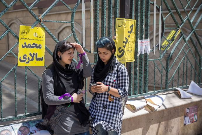 FILE PHOTO: Iranian Girls use their smartphones to follow election news in Tehran, Iran May 17, 2017. REUTERS