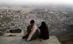 FILE PHOTO: An Iranian couple sit overlooking the city of Tehran. REUTERS/Morteza Nikoubazl/Files