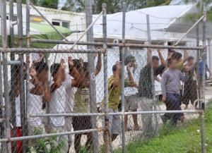 Asylum-seekers look through a fence at the Manus Island detention center. Eoin Blackwell/REUTERS.
