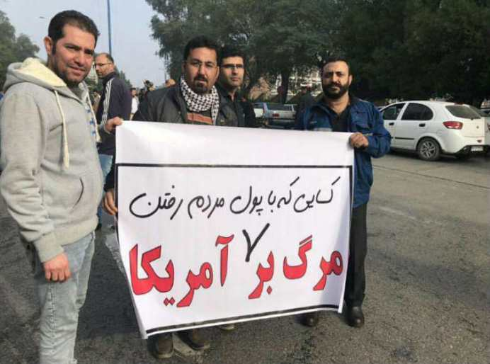 """Source: Kayhan London. The banner reads: not death to America, """" death to those that with our money travelled to the US."""" *In regime's sponsored gatherings such as Friday prayers, participants regularly chant """" death to America"""" **It refers to regime's officials and their relatives that can easily travel to the US and Europe."""