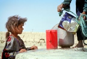 A six-year-old girl watches water pour into a pitcher at a village well outside Zabol in south eastern Iran Sistan-Baluchistan. Reuters