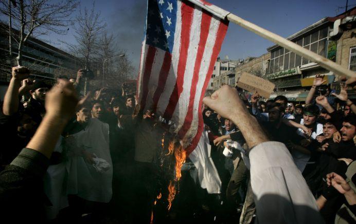 FILE PHOTO: In state-sponsored rallies participants burn U.S. flag. REUTERS/Morteza Nikoubaz