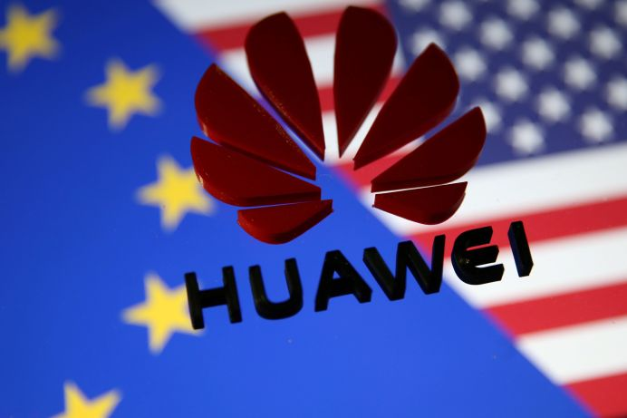 A 3D printed Huawei logo is placed on glass above displayed EU and US flags in this illustration taken January 29, 2019. REUTERS