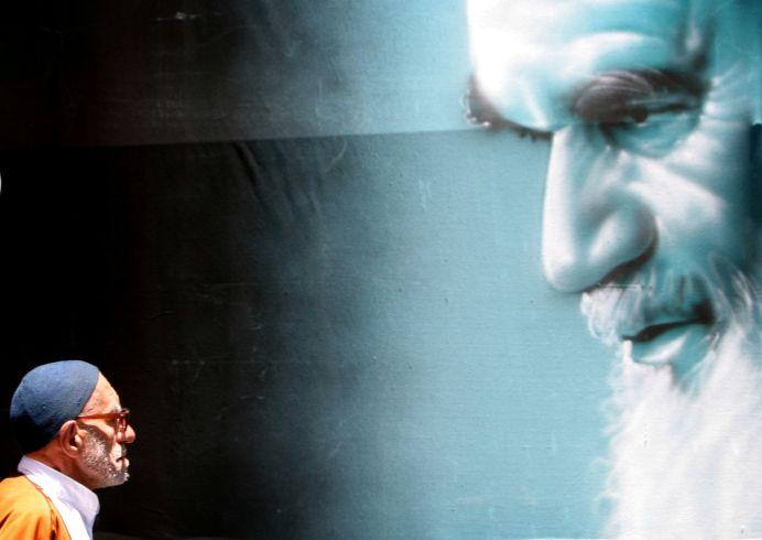 FILE PHOTO: An elderly Iranian man walks past a large poster of Iran's late leader Ayatollah Ruhollah Khomeini. REUTERS/Morteza Nikoubazl