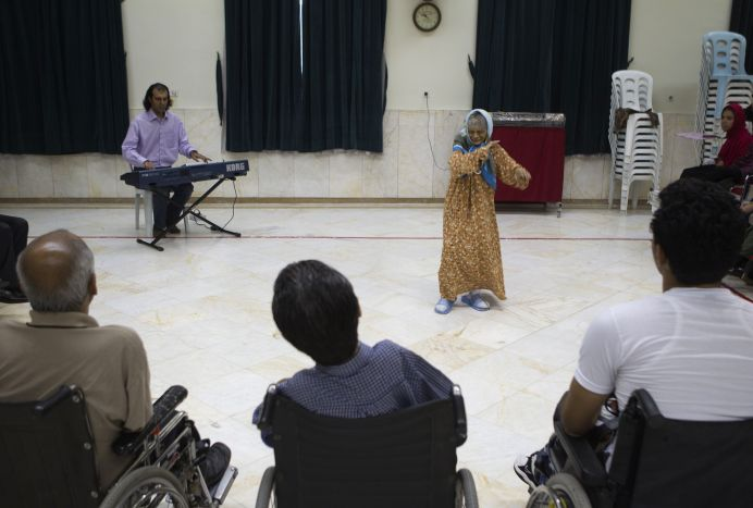FILE PHOTO: Iranian music therapist Sadeq Jafari (background, L) plays the keyboard for his disabled students at the Kahrizak nursing home, in southern Tehran. REUTERS