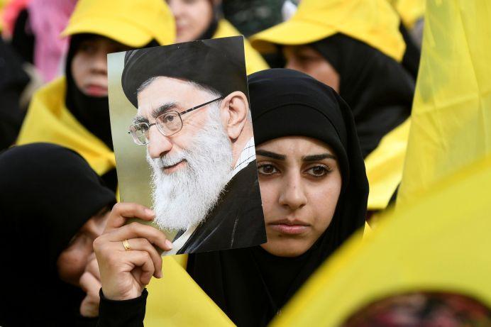 A woman carries a picture of Iran's Supreme Leader Ayatollah Ali Khamenei