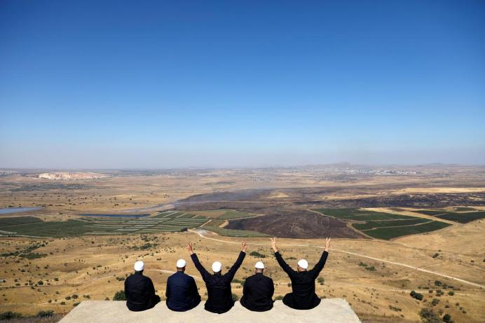 FILE PHOTO: Israeli Druzes sit together watching the Syrian side of the Israel-Syria border on the Golan Heights, Israel July 7, 2018. REUTERS/Ronen Zvulun/File Photo