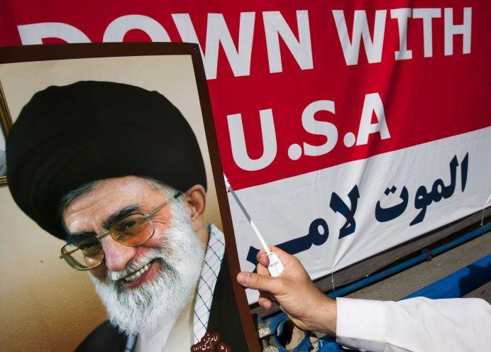 FILE PHOTO: A man holds a portrait of Iran's Supreme Leader Ayatollah Ali Khamenei. Reuters