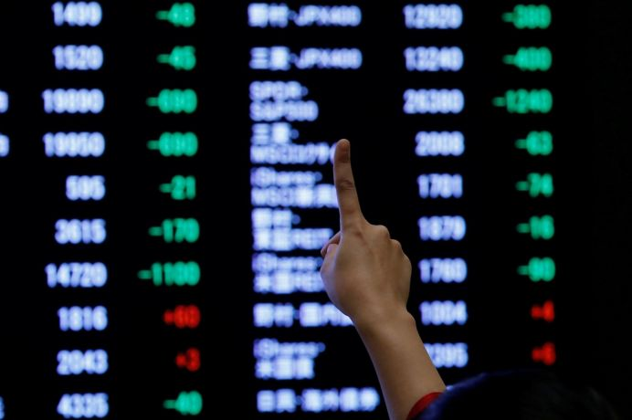 FILE PHOTO: A woman points to an electronic board showing stock prices as she poses in front of the board after the New Year opening ceremony at the Tokyo Stock Exchange (TSE), held to wish for the success of Japan's stock market, in Tokyo, Japan, January 4, 2019. REUTERS/Kim Kyung-Hoon