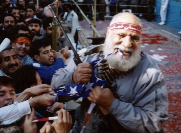 FILE PHOTO: Haj Bakhshi, a well known hardliner, tears an American flag with his teeth during a demonstration in front of the former American Embassy in Tehran, Iran. REUTERS