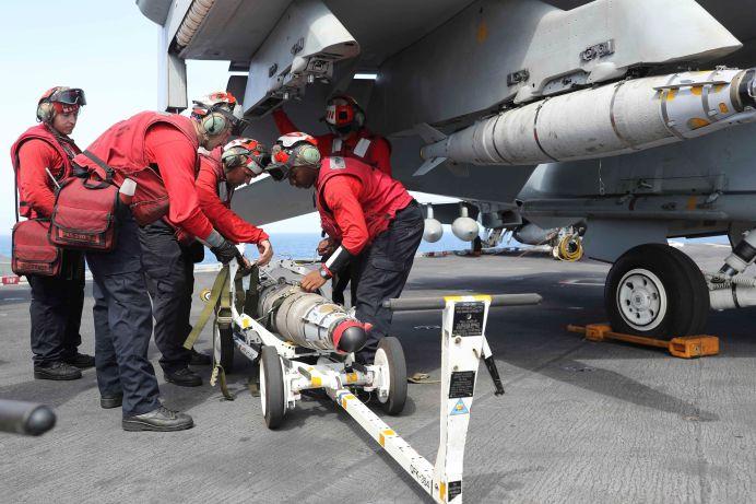 Flight dec crew remove ordnance from an F/A-18E Super Hornet on the flight deck of the aircraft carrier USS Abraham Lincoln (CVN 72), in Arabian Sea, May 22, 2019. Matt Herbst/U.S. Navy/REUTERS