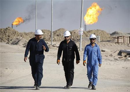 FILE PHOTO: Iraqi workers walk in West Qurna oilfield in Iraq's southern province of Basra. REUTERS/Atef Hassan