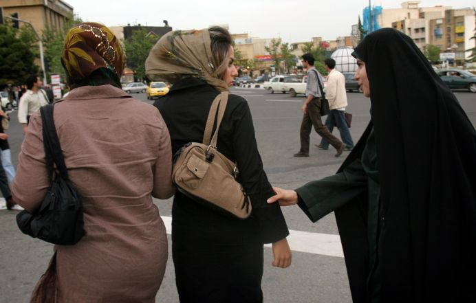 FILE PHOTO: An Iranian policewoman (R) approaches a girl in Iran, Reuters.