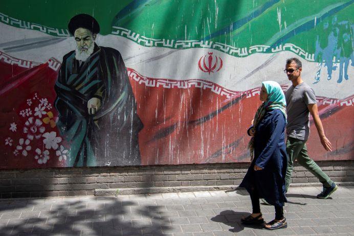 FILE PHOTO: People walk in front of a mural of Iran's late leader Ayatollah Ruhollah Khomeini in Tehran, Iran July 7, 2019. REUTERS./