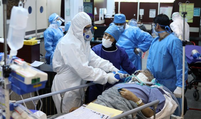 FILE PHOTO: Emergency medical staff and nurses wearing protective suits, help while transferring a patient with coronavirus disease (COVID-19) to Masih Daneshvari Hospital, in Tehran, Iran March 30, 2020. REUTERS./