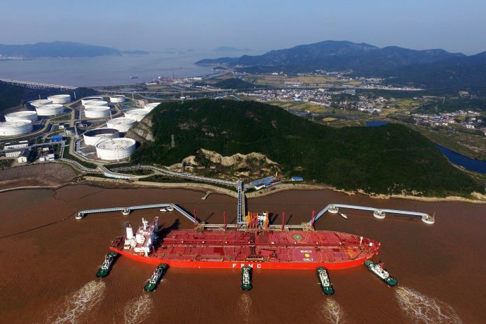 FILE PHOTO: Tugboats dock an oil tanker on a crude oil quay at the Port of Zhoushan in Zhoushan city, east China's Zhejiang.