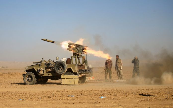 Shi'ite fighters fire a rocket towards Islamic State militants during a battle with Islamic State militants at the airport of Tal Afar, west of Mosul, Iraq, November 18, 2016.