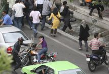FILE PHOTO: Riot police hits a motorcyclist with a baton during a protest in Iran. Reuters./
