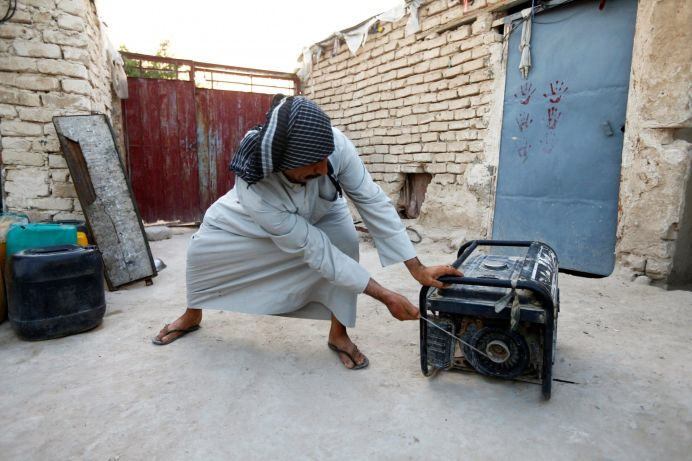 FILE PHOTO: A man tries to run his personal electrical generator at home, after continuous power outages in the holy city of Najaf, Iraq July 14, 2020.REUTERS/Alaa Al-Marjani