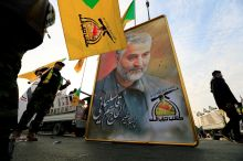 FILE PHOTO: Kataib Hezbollah Iraqi militia hold the picture of the Iranian Major-General Qassem Soleimani, as they gather ahead of the funeral of the Iraqi militia commander Abu Mahdi al-Muhandis, who was killed in an air strike at Baghdad airport, in Baghdad, Iraq, January 4, 2020. REUTERS/Thaier al-Sudani