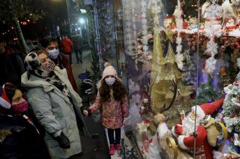 An Iranian family look at a Showcase of a Christmas store in Tehran, Iran December 23, 2020. REUTERS./
