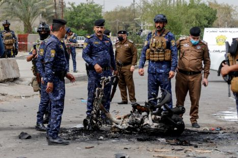 FILE PHOTO: Members of security forces inspect the scene of an explosion in Baghdad, Iraq March 23, 2021. REUTERS/Khalid al-Mousily/File Photo