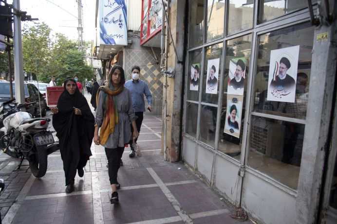 (6/4/2021) Two Iranian women walk past a campaign center for the conservative politician, head of Iran's judiciary, and Iran's June 18 presidential elections candidate Ebrahim Raisi in southwest of Tehran. REUTERS./