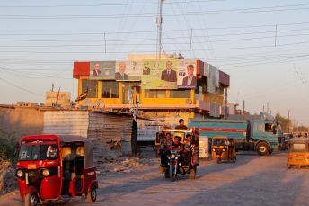 Tuk-tuk drivers pass by election campaigns posters ahead of the parliamentary election, in Baghdad, Iraq September 27, 2021. Picture taken September 27, 2021. REUTERS/Ahmed Saad
