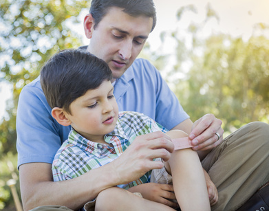 Loving Father Puts a Bandage on the Knee of His Young Son in the Park.