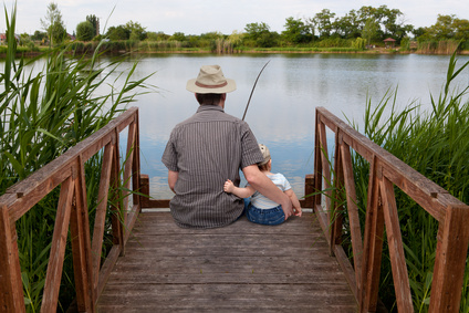 father with little son fish on the shore of Lake