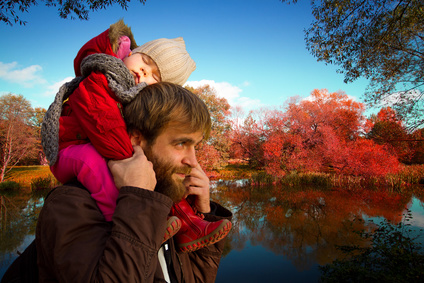 Dad and daughter. daughter fell asleep on his neck with his father in autumn park