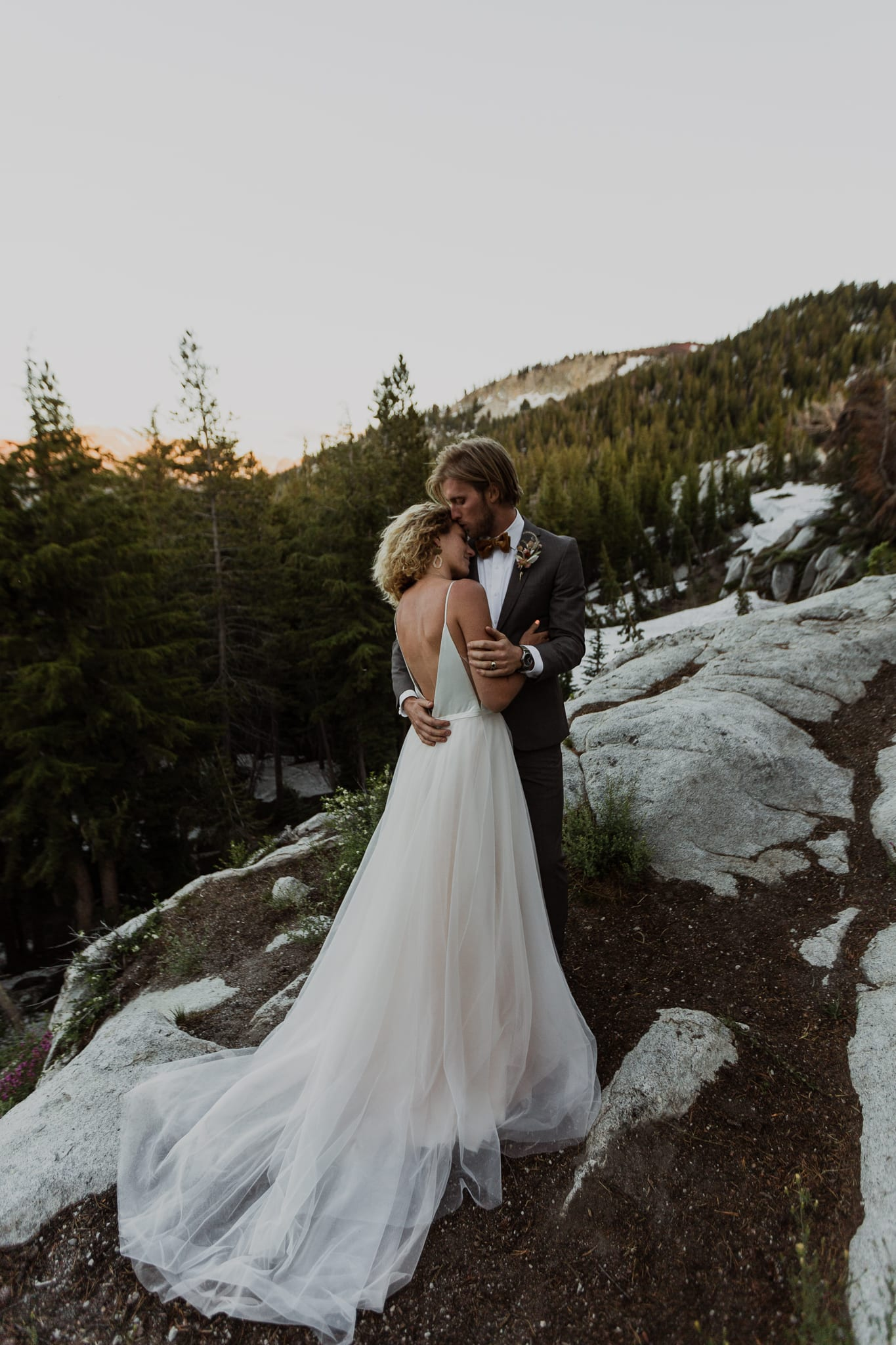 Tyler kisses Haylee on the forehead as she rests her head on his chest. They're standing on rocks overlooking the Mammoth Valley.