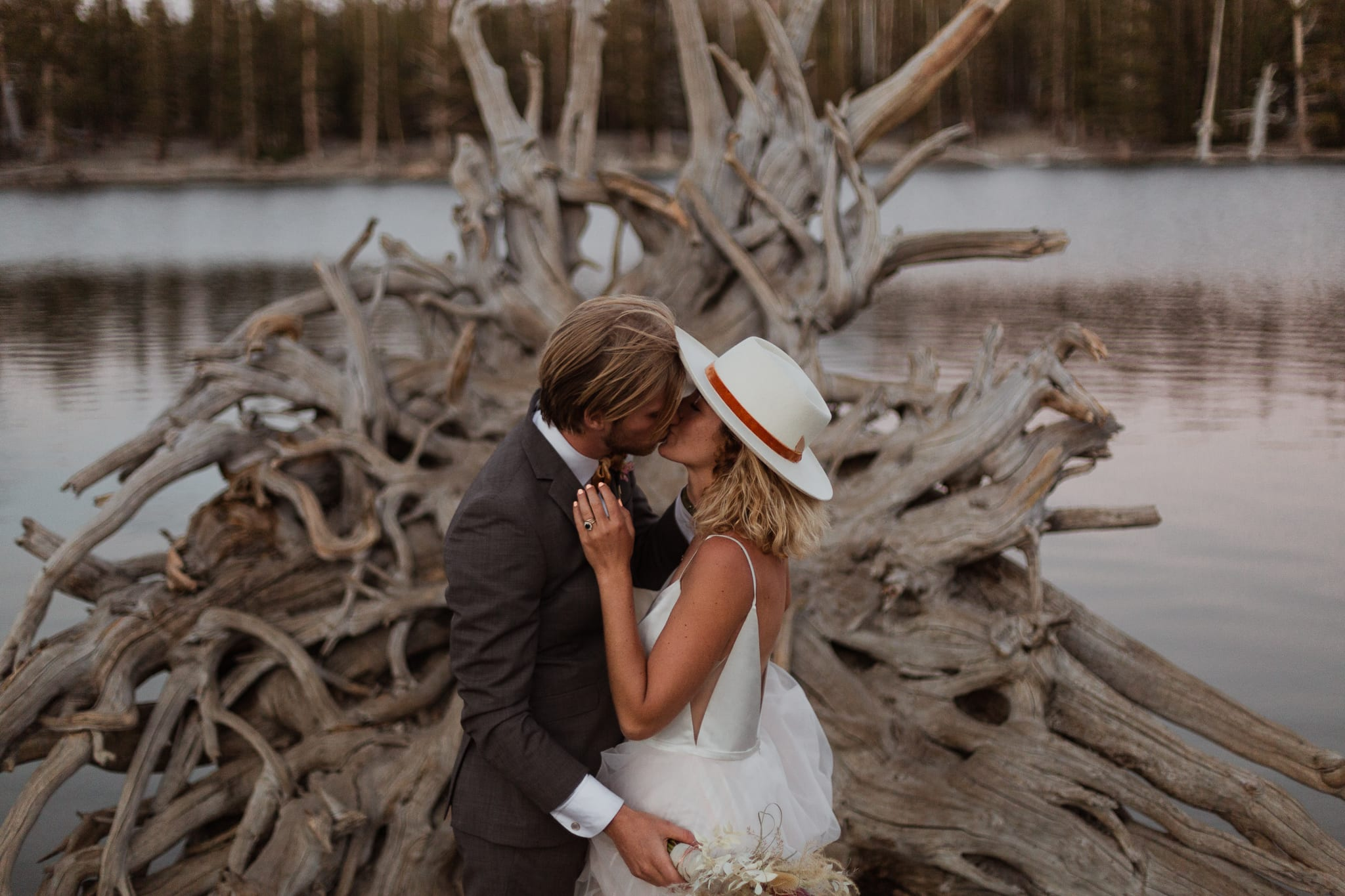 Tyler and Haylee kiss in front of fallen tree at Horseshoe Lake.