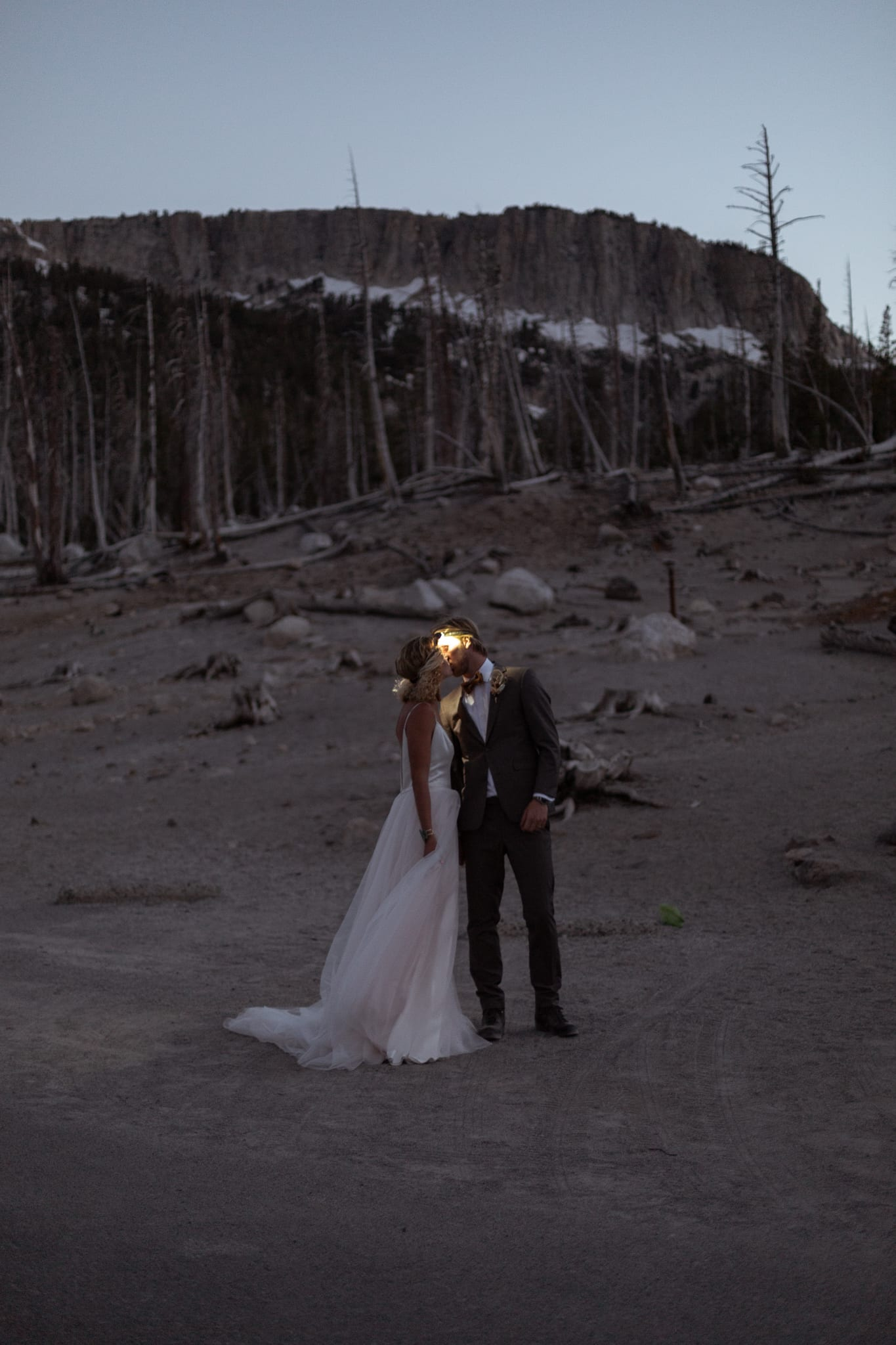 Tyler and Haylee share a kiss at night while the light from the headlamps they are wearing light up their faces.