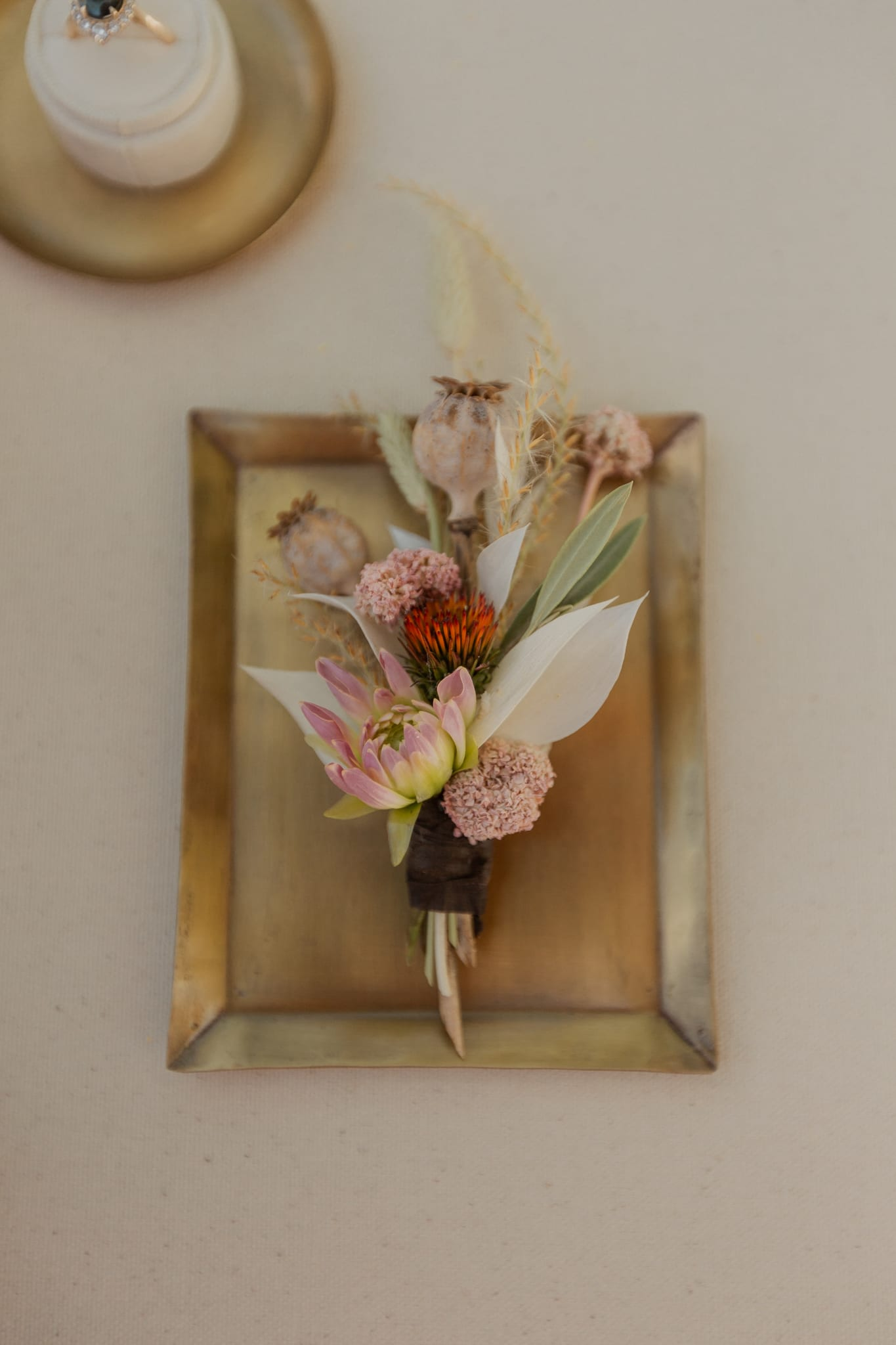 Tyler's blush, white and green boutonniere rests atop a rectangular gold plate.