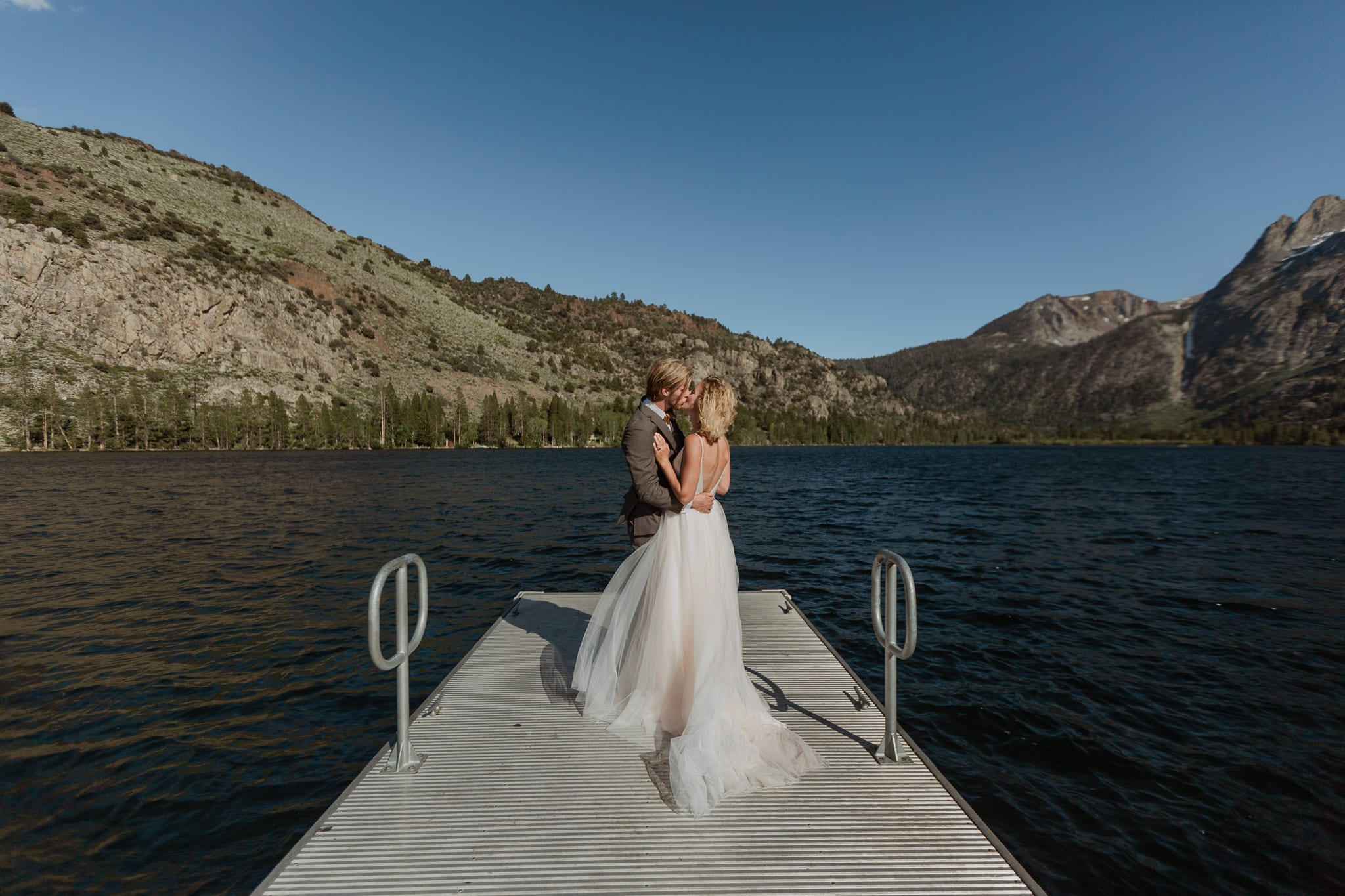 Tyler and Haylee stand hugging at the end of the Silver Lake dock on their elopement day.