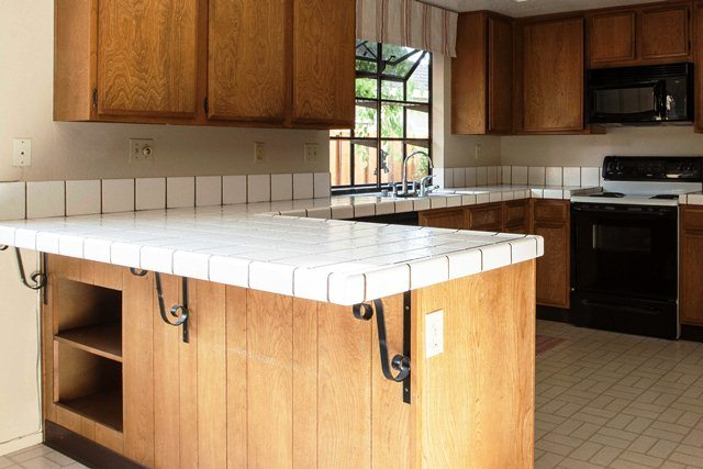 Cantilevered tile countertop with corbels underneath for support.