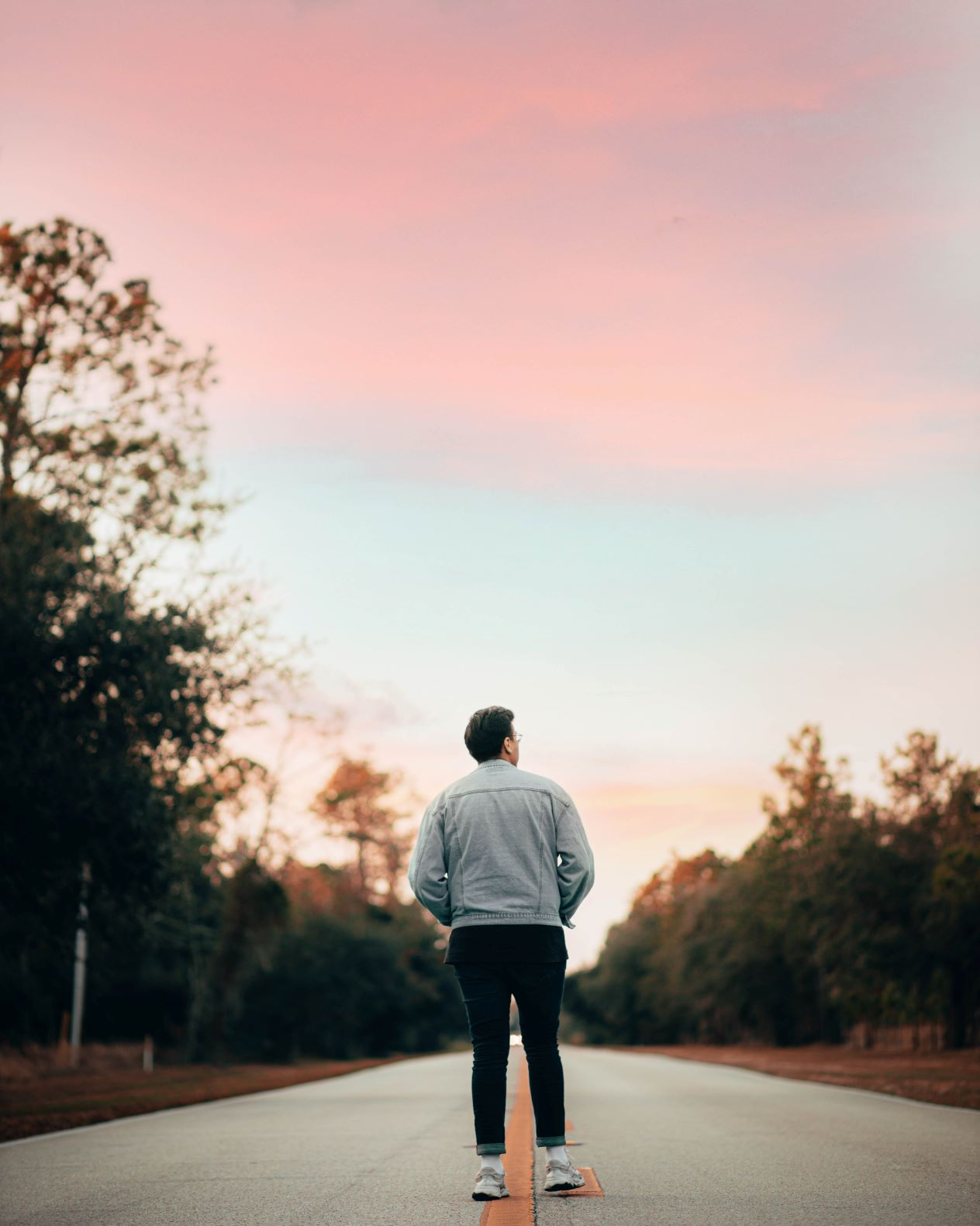 the back on a person standing on a road looking at a pink sky