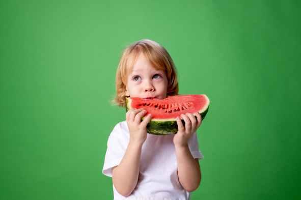 girl in white long sleeve shirt eating watermelon