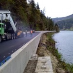 Crews put the finishing touches on paving the surface of a 1,130 foot bridge, the longest in the Lane County road system, that spans dry ground next to the Siuslaw River on Sweet Creek Road. (photo by Lane Count Public Works.)