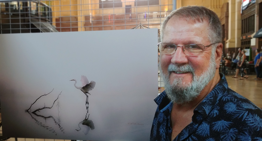 Carl D'Amico next to one of his composite images on display at the 2019 Fringe Festival KC Visual Arts Exhibition at Union Station (Photo by <i>Mugur Geana</i>)