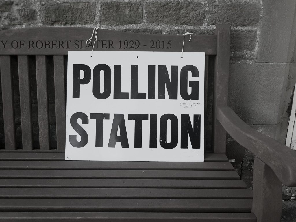 Photo of polling station sign on bench