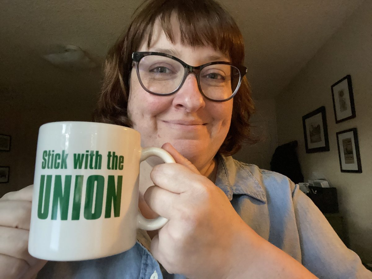 """Outgoing President Carrie Rolph drinking from her """"Stick with the Union"""" mug"""